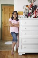 Smiling Hispanic girl posing in doorway
