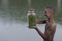 African boy holding insect jar