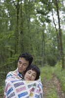 Asian couple wrapped in blanket in forest