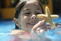 Girl holding starfish in swimming pool
