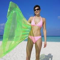 Woman holding pool raft at beach