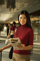 Asian woman holding newspaper