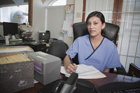 Hispanic doctor completing paperwork in office