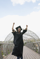 Mixed race graduate in cap and gown cheering