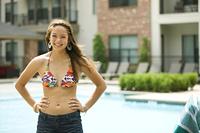 Mixed race girl wearing bikini standing near swimming pool