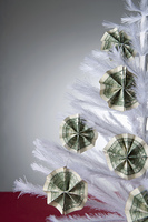 Cash ornaments on white, artificial Christmas tree