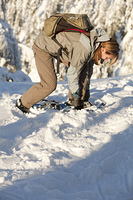 Caucasian woman fixing snowshoes in snow