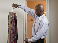 African American businessman picking tie