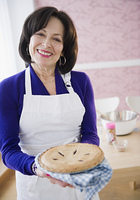 Mixed race woman holding fresh baked pie