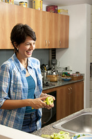 Hispanic woman peeling apple in kitchen