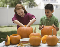 Children carving Halloween pumpkins together