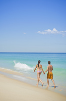 Caucasian couple walking on beach together