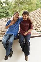 Hispanic boys sitting on roof hugging