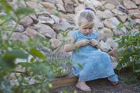 Serious Caucasian girl picking vegetables in garden