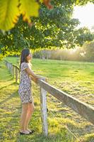 Hispanic woman leaning on field fence