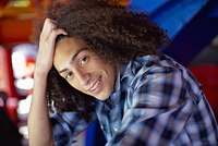 Smiling mixed race teenager with head in hands