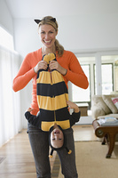Caucasian mother playing with baby daughter in bee costume