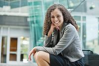Smiling Caucasian businesswoman sitting outdoors