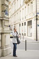 Hispanic woman using cell phone in city sidewalk