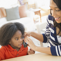 African American mother and son using telephone
