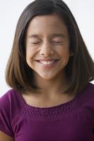 Smiling Hispanic girl with eyes closed