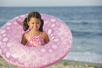 Smiling girl holding inflatable ring on beach
