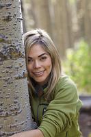 Hispanic woman hugging tree in forest