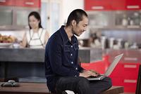 Japanese man using laptop in kitchen