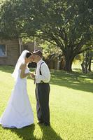Hispanic grandfather giving bride a kiss