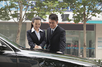 Chinese business people standing near car working