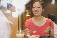Chinese woman eating in cafe