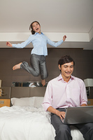 Chinese woman jumping on bed behind working boyfriend