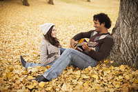 Man playing guitar for girlfriend in autumn leaves