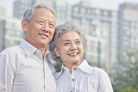 Older Chinese couple standing on city street
