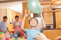 Chinese girl holding balloon at birthday party