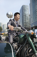 Chinese businessman riding motorcycle with sidecar