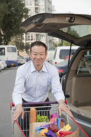 Chinese man packing groceries into car