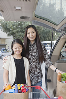 Chinese mother and daughter packing groceries into car