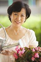Older Asian woman watering flowers in garden