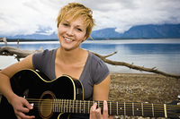 Caucasian woman playing guitar near lake