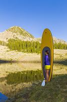 Hispanic woman with paddle board in rural landscape