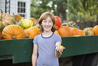 Caucasian girl holding miniature gourd at pumpkin patch