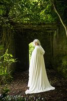 Caucasian woman wearing white cloak in garden