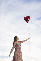 Woman holding heart-shaped balloon