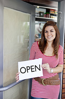 Hispanic woman holding 'open' sign in door