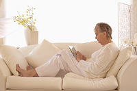 Older Caucasian woman using tablet computer on sofa