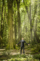 Caucasian businessman standing in forest