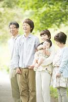 新緑の中で微笑む3世代家族