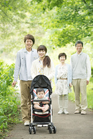 新緑の中で散歩をする3世代家族
