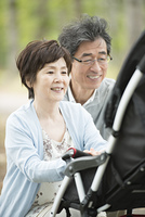 ベビーカーに乗る孫を見て微笑む祖父母